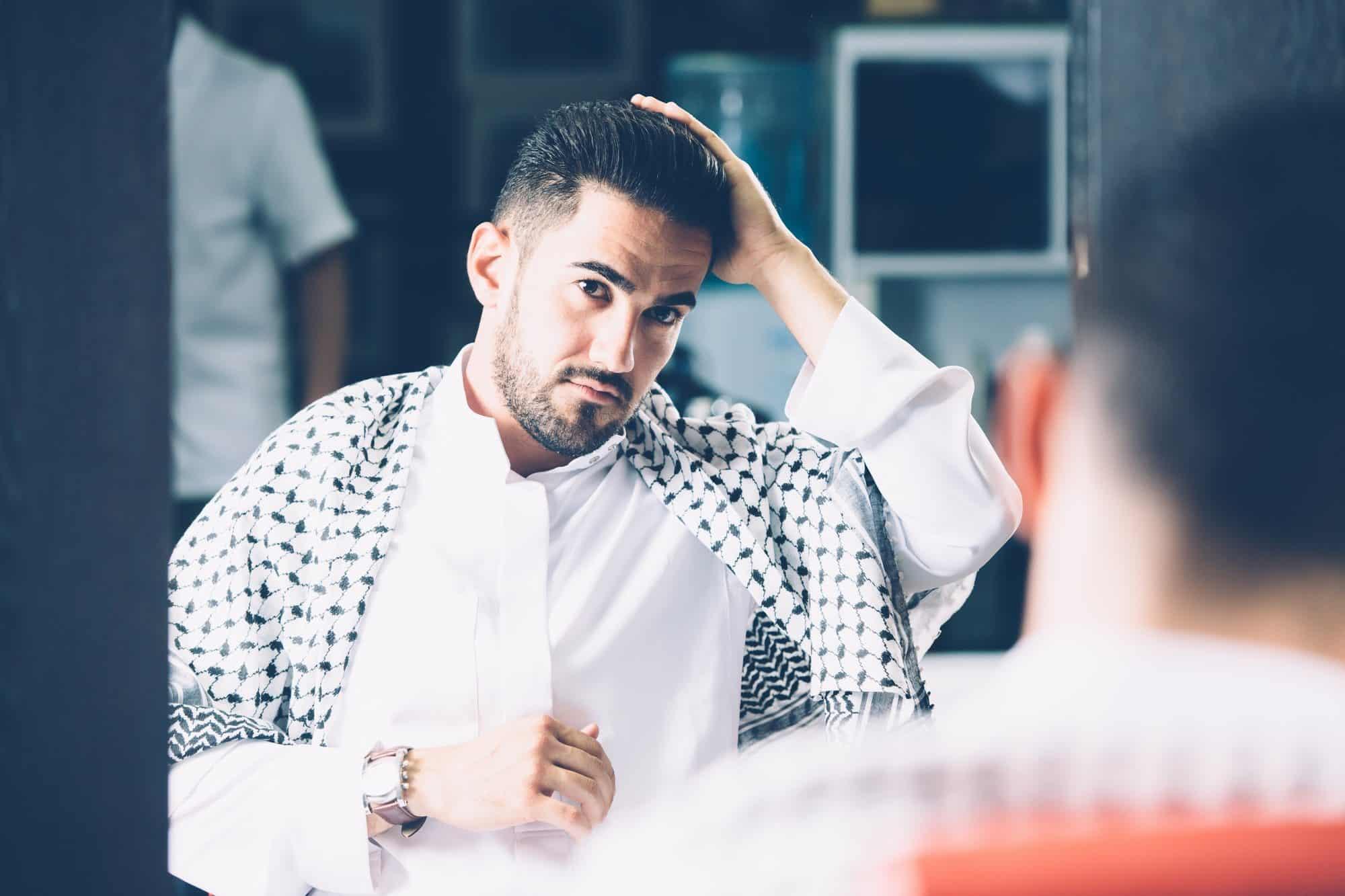 Man touching hair in barbershop